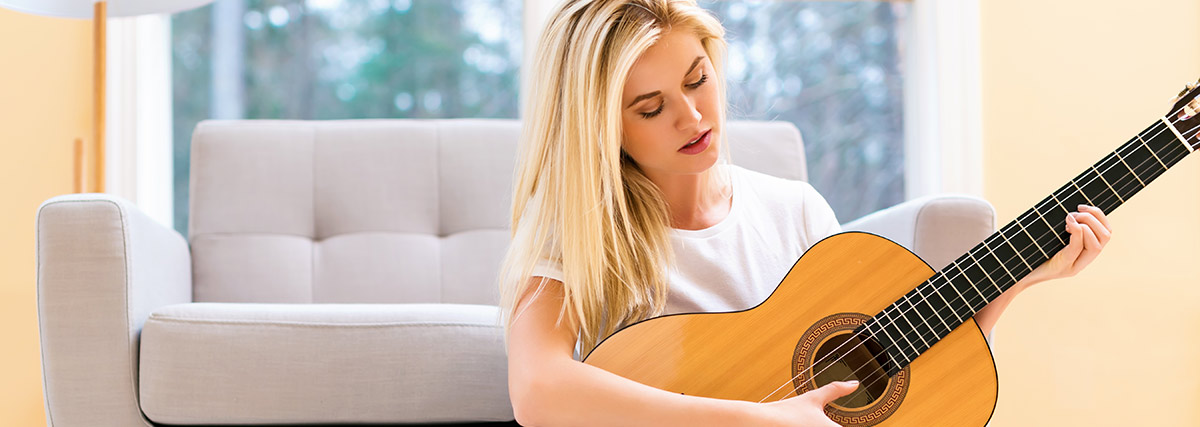Blond lady playing classical guitar