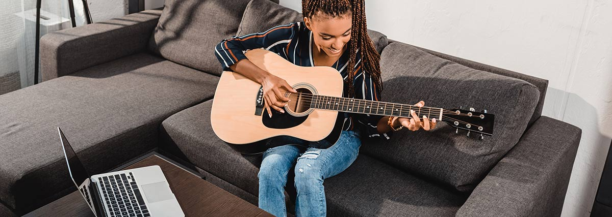 Young lady attending Skype guitar lesson